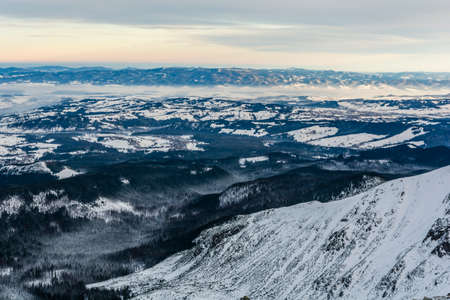 Winter landscape of mountain and lowland seen from the peak in the Tatra Mountains in the morning.  Stock Photo