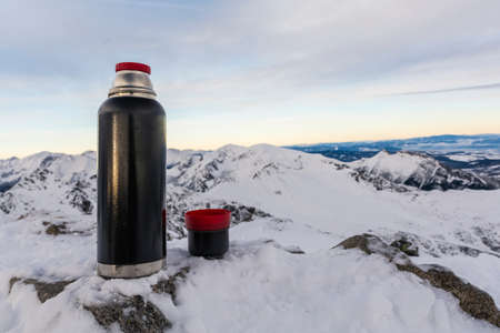 giewont: Cup of hot tea from a tumbler in winter in the mountains. Stock Photo