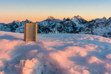 hip flask: Hip flask in a winter scenery in the mountains in the rays of the setting sun.