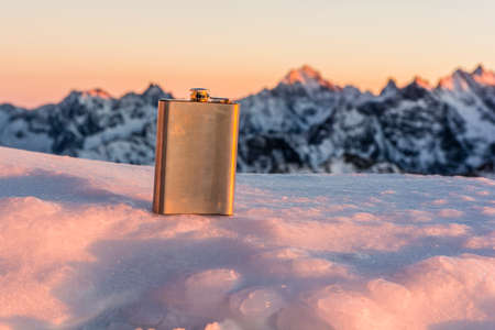 hip flask: Hip flask on a background of mountains at sunset. Stock Photo