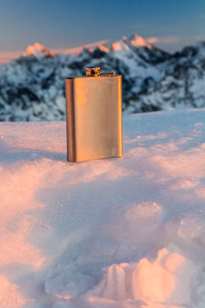Hip flask on a background of mountains in the rays of the setting sun. Stock Photo
