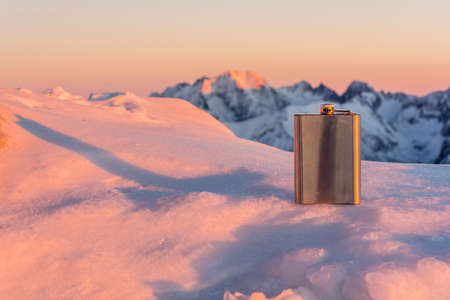 hip flask: Hip flask in the mountains at sunset.