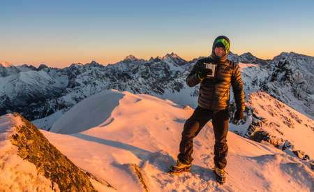 hip flask: Tourist winter with hip flask in the mountains at sunset.