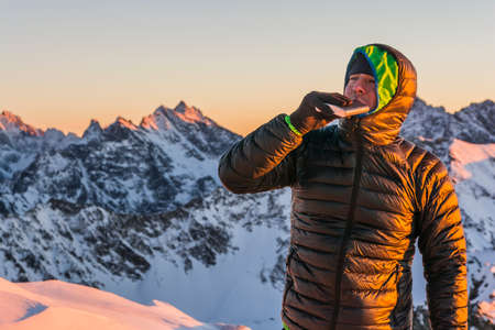 Hiker in winter drink a small sip from the hip flask in the mountains at sunset.