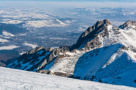 In the valley behind the peak Giewont visible is the city of Zakopane in winter. Stock Photo