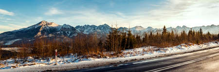 View from asphalt road to snow-capped mountain peaks.