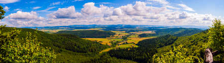 Loose residential development in a valley in the Sudetes. - Summer Panorama of forest and agricultural land. Stock Photo