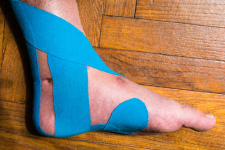 Elastic therapeutic tape (Kinesio Taping) on the left mans left ankle.