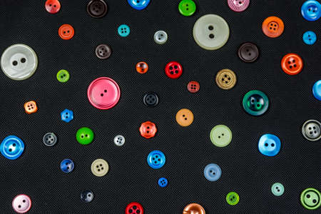 Many different colored and different sized buttons on a dark background. Stockfoto