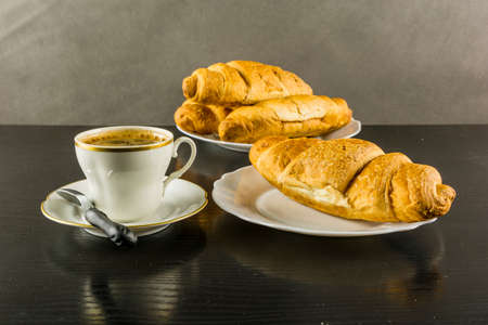 Cup of hot coffee and a croissant for breakfast.