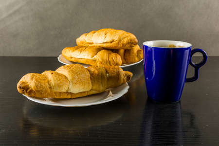 Fresh croissant and hot mug of black coffee for breakfast.