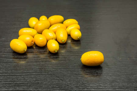 Ripe kumquat on a dark wooden table.