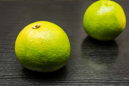 Green grapefruit variety on a wooden dark table. Stock Photo