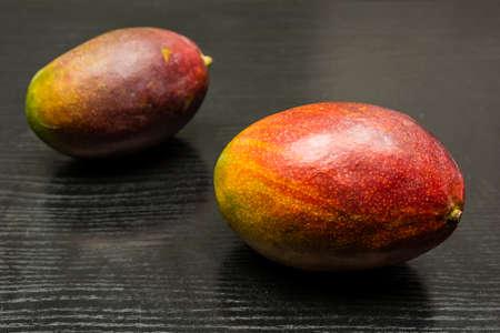 Mango fruit on a dark wooden table.