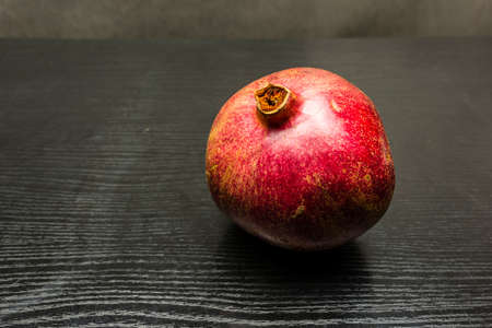 Red ripe fruit pomegranate on a dark table.