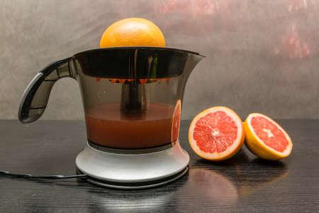 Citrus juice squeezer. Squeezed fresh grapefruit juice.