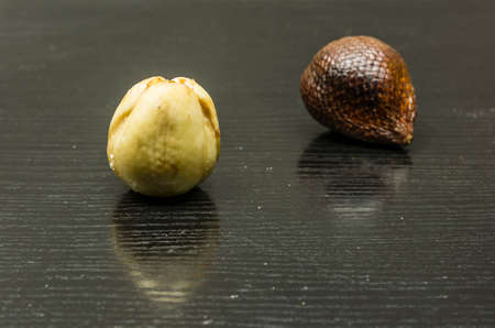 Downloaded from skin of the fruit (Salacca Zalacca) on a wooden table. Stock Photo