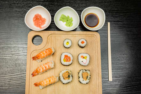 Board with a traditional sushi set and dishes with wasabi soy sauce marinated with ginger.