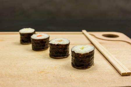 Four hosomaki and chopsticks on a wooden board.