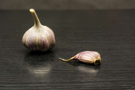 Clove and bulb garlic (Allium sativum) on the table. Imagens