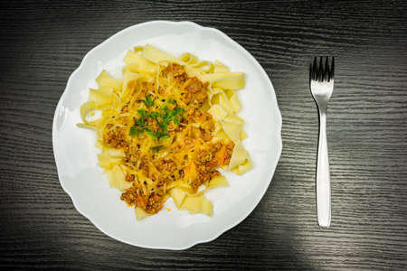 Pasta with minced meat and grated yellow cheese on a white plate and a fork on the side on a wooden table. View from above.