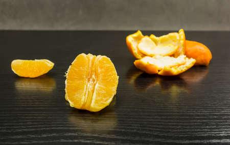 Peeled and split orange on a dark table.
