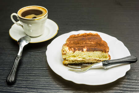 Italian specialty - sweet Tiramisu dessert and a cup of coffee. Stock Photo