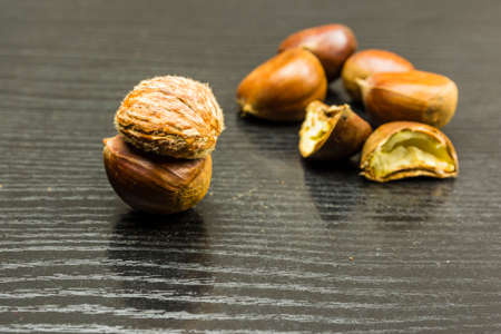 Peeled chestnut all over on a wooden table. In the background, cross and whole chestnuts.
