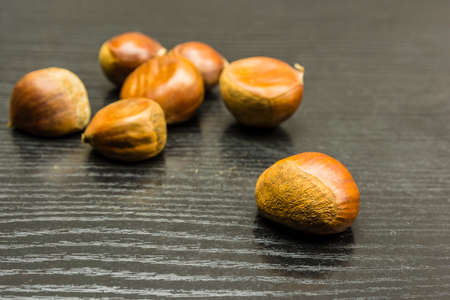 Ripe chestnut on a wooden dark table. In the background, whole chestnuts.