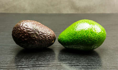 Hass and Choquette avocado on a wooden dark table. Stock Photo