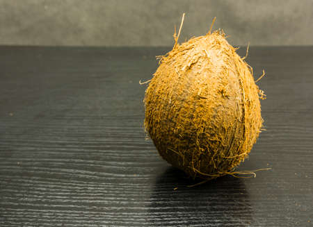 Ripe fruit of palm (coconut) on a wooden table. Stock Photo