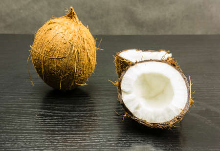 Cleaved fruit of palm (coconut) on a wooden table.