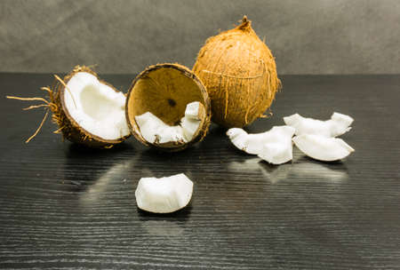 Edible part of a coconut on a wooden table. In the background, a whole and broken coconut. Stock Photo