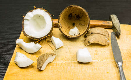 Coconut and tools for its opening on the board.