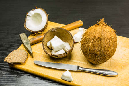 Whole coconut and broken with tools to open it on a board on the table. Stock Photo