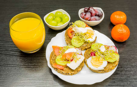 A healthy breakfast that is a plate of rye bread sandwiches with fresh vegetables, salmon, yak, sprouts, cheese and mayonnaise. As a snack fruit and juice from freshly squeezed oranges for drinking.