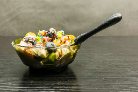 Teaspoon immersed in a bowl with ice cream dessert on a wooden table. Imagens