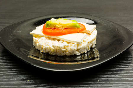 Rice cake sandwich with cheese (Camembert), tomato and avocado on a black plate. Stock Photo