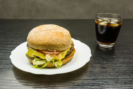 Beef burger and a glass of cola with ice on a wooden table.