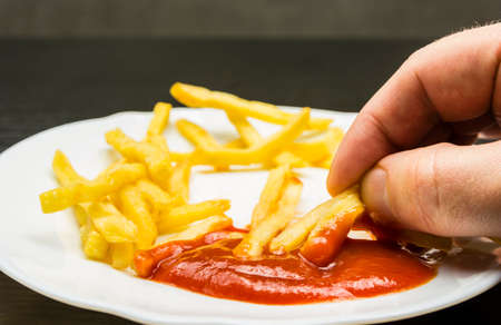 French fries dipped in ketchup on a plate on a wooden table. Banque d'images