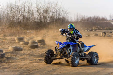 Biskupice Radlowskie, Poland - January 14, 2018: ATV racer takes a turn during a race on a dusty terrain. Editorial