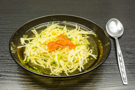 Plate of chicken noodle soup with orange carrot and green parsley.
