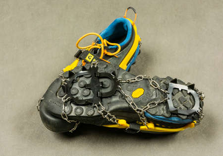 Niedomice, Poland - February 14, 2018: Approach shoes (La Sportiva TX4) with anti-slip crampons (Grivel Ran).