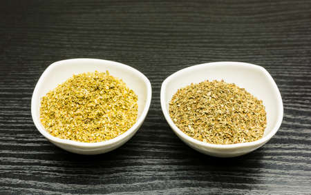 White bowls with dried herbs - basil and oregano - on a dark table.