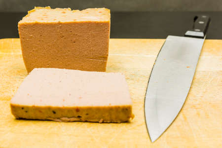 Baked pate and knife on a wooden board.