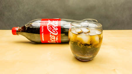 Niedomice, Poland - March 09, 2018: A glass of Coca-Cola with ice cubes. Bottle in the background.