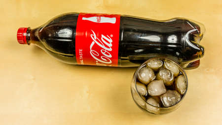 Niedomice, Poland - March 09, 2018: Traditional Coca-Cola in a glass with ice cubes. View from above.