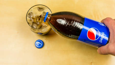 Niedomice, Poland - March 09, 2018: Pouring a glass of Pepsi from the bottle.
