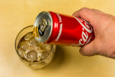 Niedomice, Poland - March 09, 2018: Pouring Coca-Cola from a can into a glass with ice cubes. Editorial