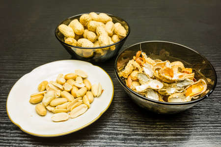 Shelling peanuts, nutshell in a bowl and clean peanuts on the plate. Stock Photo